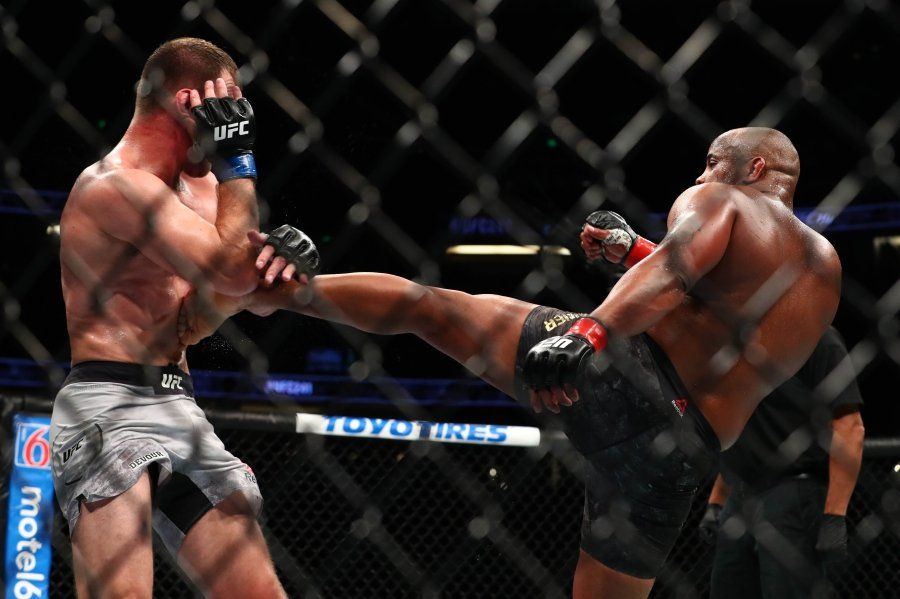 ANAHEIM, CALIFORNIA - AUGUST 17: Daniel Cormier sends a kick to Stipe Miocic in the third round during their UFC Heavyweight Title Bout at UFC 241 at Honda Center on August 17, 2019 in Anaheim, California. - Joe Scarnici/Getty Images/AFP