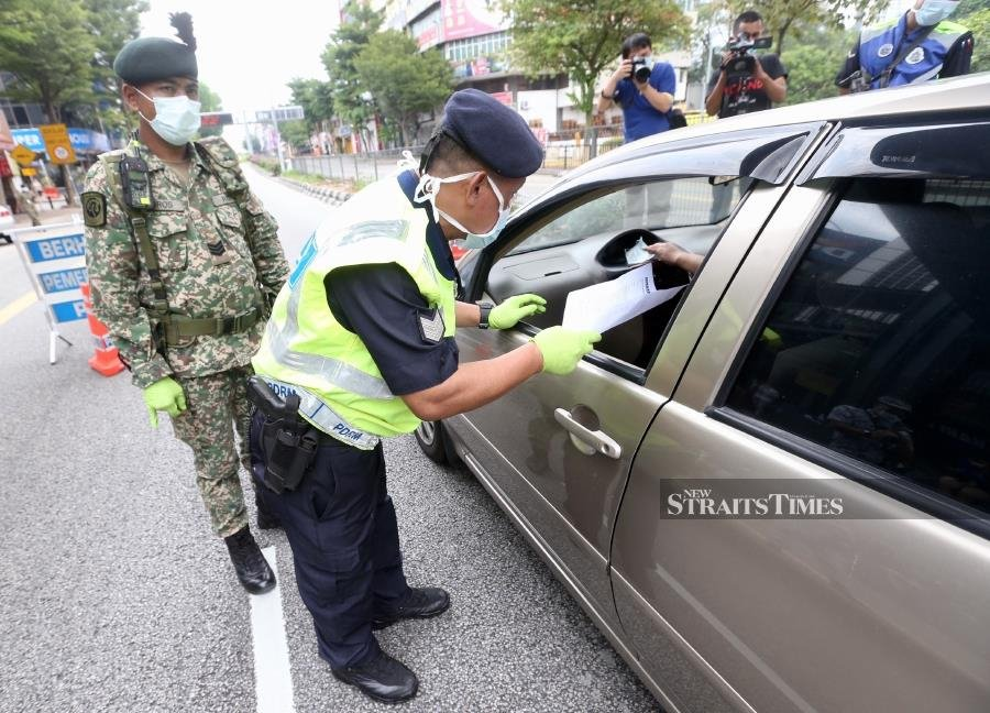 FILE PIX: A policeman questioning a motorist at a roadblock in Jalan Ipoh, Kuala Lumpur during the enforcement of Movement Control Order recently. -- Pix: NSTP/MOHAMAD SHAHRIL BADRI SAALI