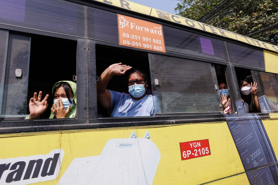 People wave and make the three-finger salute from a bus as they are released from Insein prison in Yangon on March 24, 2021, where they had been detained after taking part in demonstrations against the military coup. (Photo by STR / AFP)
