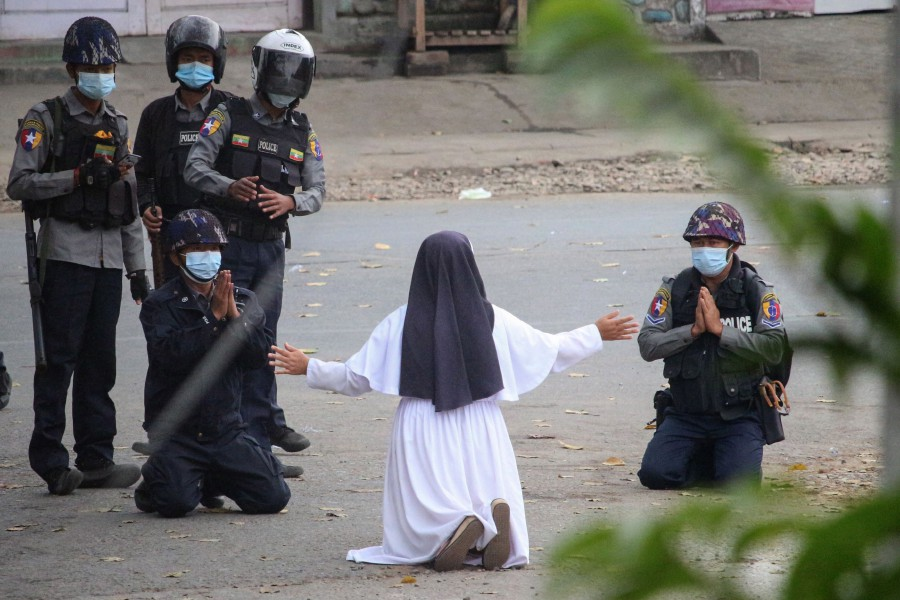 This handout photo taken on March 8, 2021 and released on March 9 by the Myitkyina News Journal shows a nun pleading with police not to harm protesters in Myitkyina in Myanmar's Kachin state, amid a crackdown on demonstrations against the military coup. (Photo by Handout / Myitkyina News Journal / AFP)