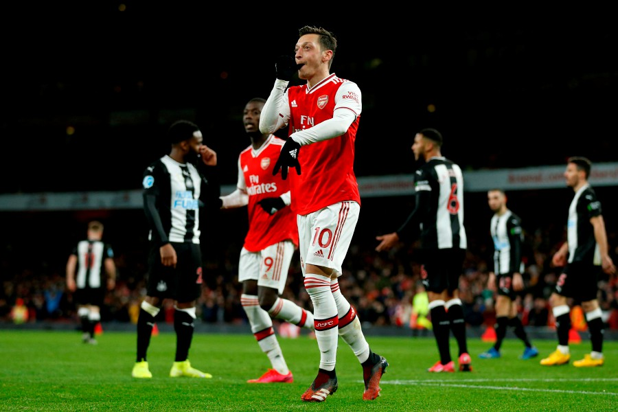 Arsenal's Mesut Ozil (centre) celebrates after scoring their third goal. -AFP