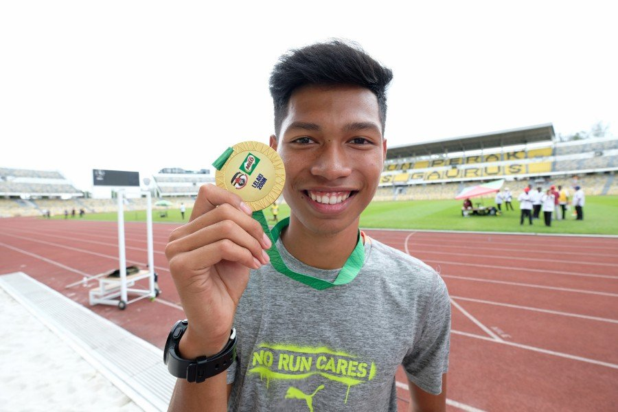 Muhammad Azeem Mohd Fahmi shows his medal after winning the men's 200 metres race and setting a new record in Ipoh. -Bernama