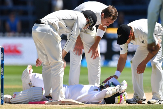 Bangladesh's Mushfiqur Rahim is checked by New Zealand's Tom Latham (L), Tim Southee (C) and Neil Wagner (R) after Rahim was hit in the head during day five of the first international Test cricket match between New Zealand and Bangladesh at the Basin Reserve in Wellington on January 16, 2017. AFP Photo