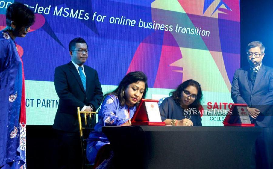 NAWEM president Sarojini Ruth (left) and Saito deputy vice-chancellor Professor Dr Vinitha Guptan (right) signing a memorandum of understanding, witnessed by HRDF R&D head Rony Ambrose Gobilee recently. -- Pix courtesy of NAWEM