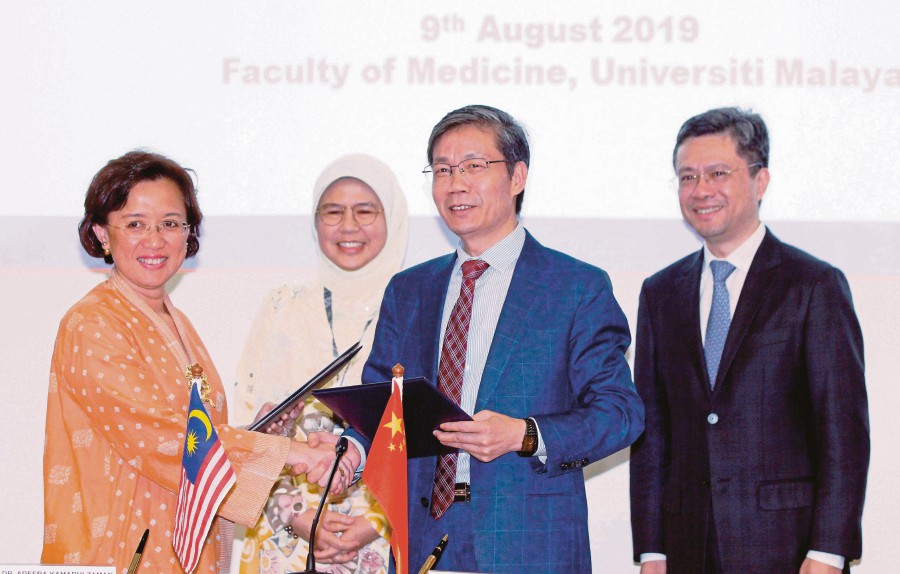 Professor Dr Chen Guoqiang (second from right) exchanging documents with Professor Datuk Dr Adeeba Kamarulzaman at the MoU signing ceremony between UM and Shanghai Jiao Tong University School of Medicine recently. Looking on are Professor Dr Kamila Ghazali (second from left) and Professor Xia Qiang. -- PIC BY MUSTAFFA KAMAL
