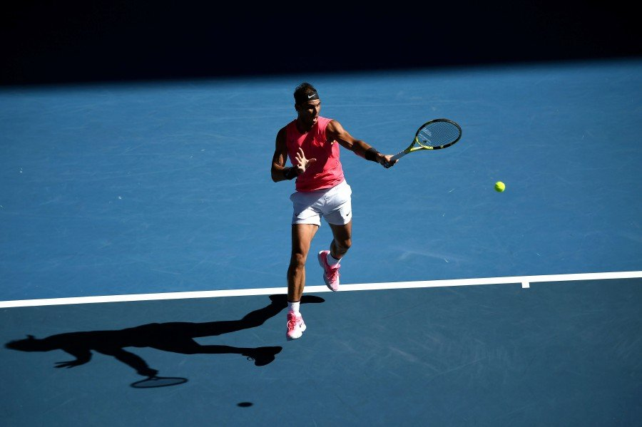 Rafael Nadal hits a return against Pablo Carreno Busta during their men's singles match on day six of the Australian Open tennis tournament in Melbourne. -AFP