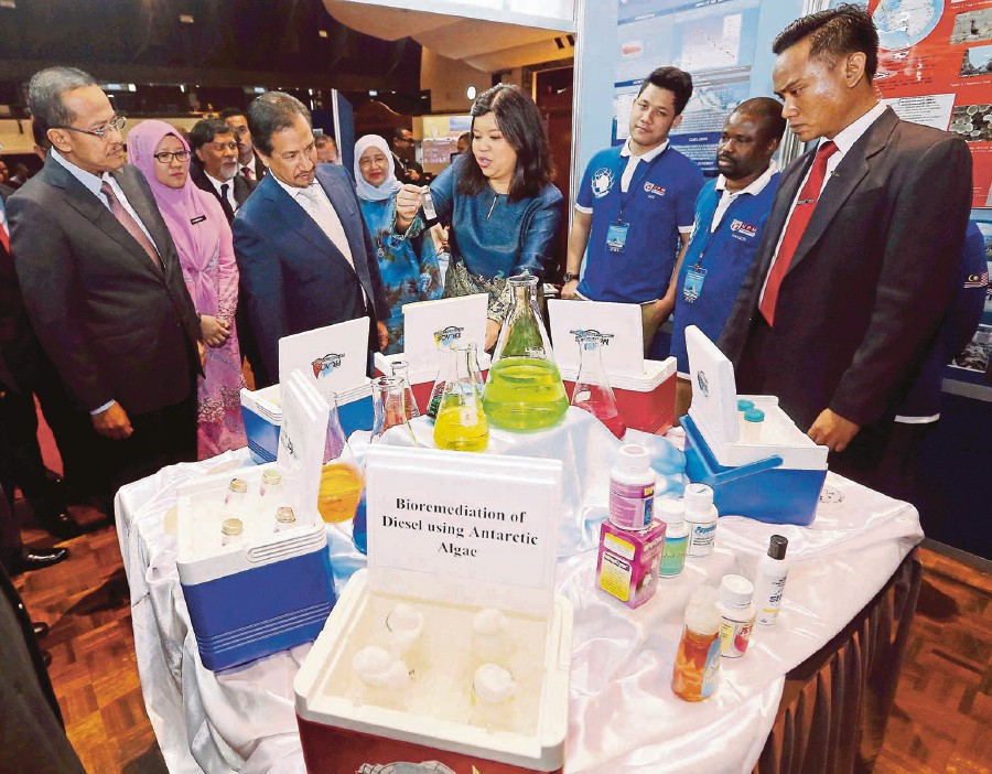 Sultan Mizan Zainal Abidin (second from left) listens to Siti Aqlima Ahmad (centre) explain her research project after the opening of the 8th Malaysian International Seminar on Antartica in UPM.