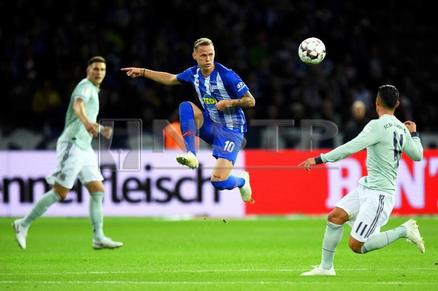 tha Hertha Berlin's Ondrej Duda (centre) in action against Bayern Munich's James Rodriguez. - EPA