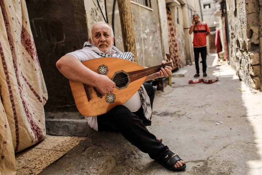 Tawfiq Shanaa, a 66-year-old man, plays the oud as he performs traditional Palestinian songs outside his house in the Rafah camp for Palestinian refugees in the southern Gaza Strip.  -AFP pic