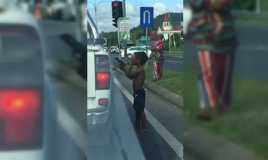 This viral image show a boy holding a toy gun while begging for money at Bandar Sri Perdana. - NSTP/Pic courtesy of police