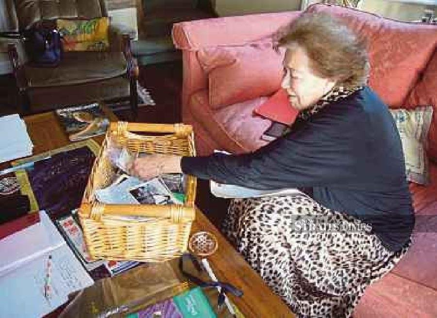 The late Datin Peggy Taylor with a collection of documents and pictures from old Malaya.