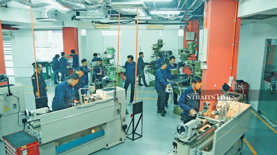 Malaysian Meister Programme students guided by a trainer on the proper technique to operate the machines.