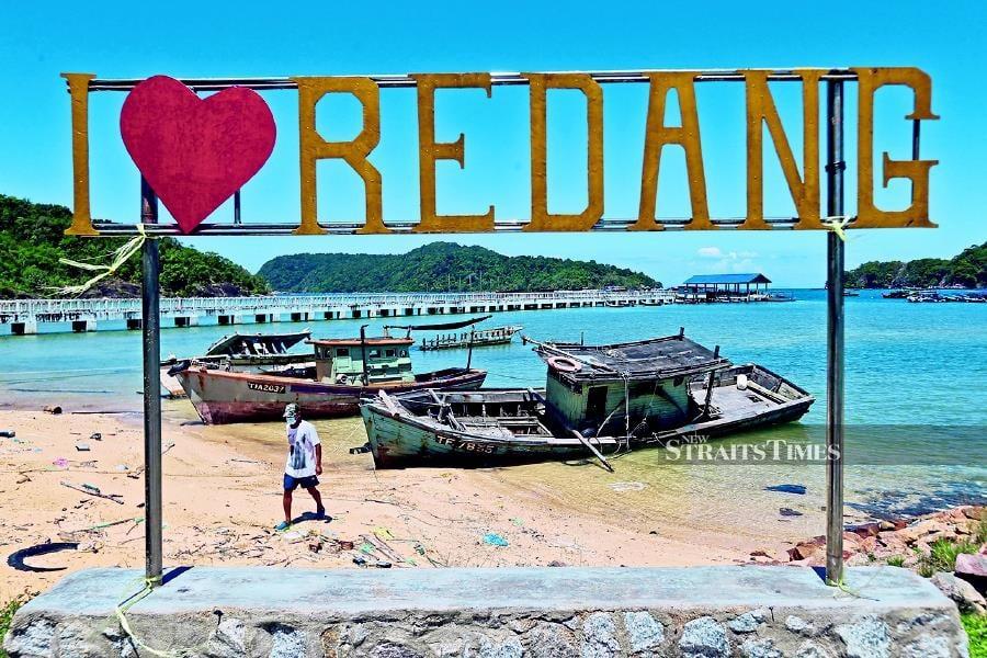 Entrepreneur Azmi Awang walking away from beached boats at the Pulau Duyong Jetty in Kuala Terengganu. Near him is a sign promoting Pulau Redang. - NSTP/GHAZALI KORI