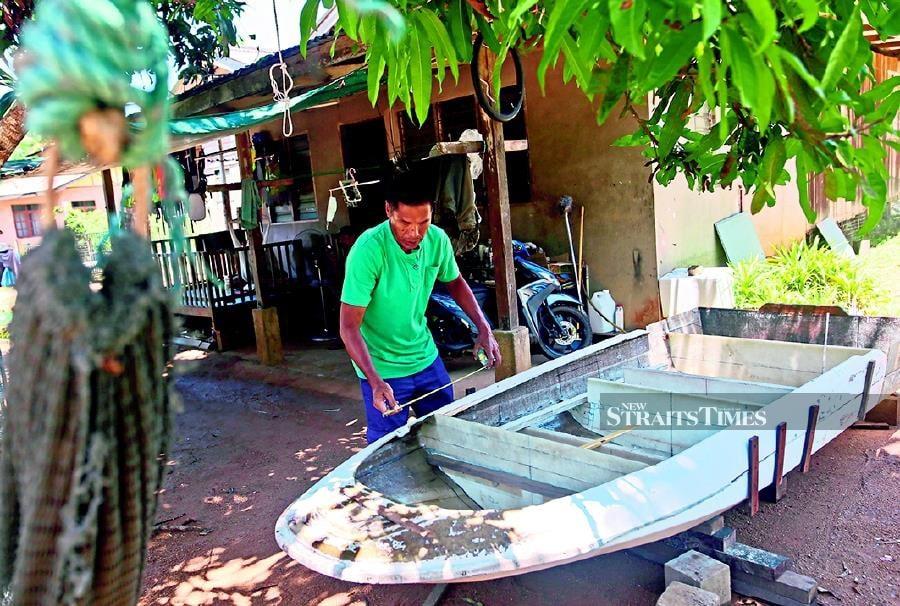 A man taking measurements of his boat for repairs in Kampung Pulau Redang.