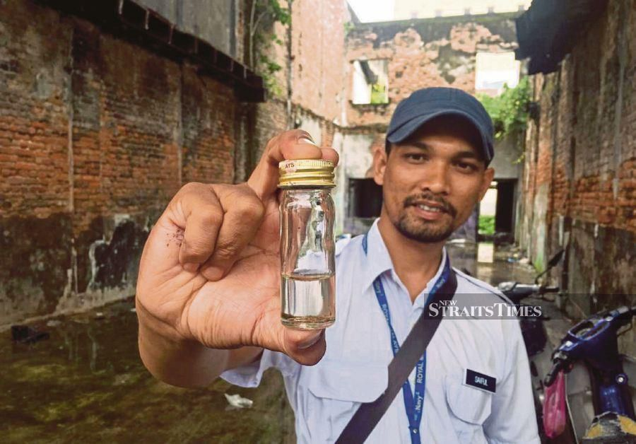 (File pix) A health department officer showing a sample taken from a site believed to be mosquito breeding area near City Plaza, Alor Star. Pix by Noorazura Abdul Rahman