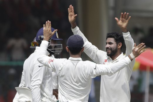 India's Ravindra Jadeja, right, and his teammates celebrates the wicket of New Zealand's Luke Ronchi on the third day of their cricket test match at Green Park Stadium in Kanpur, India. AP Photo