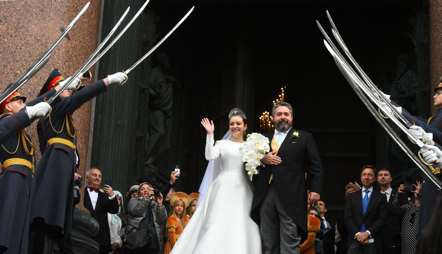 Grand Duke George Mikhailovich Romanov and Victoria Romanovna Bettarini leave the Saint Isaac's Cathedral as Russian honour guards salute them during their wedding ceremony in Saint Petersburg. - AFP PIC