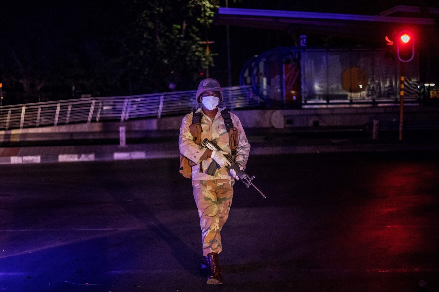 A member of the South African National Defence Force (SANDF) wearing a face mask patrols during an operation in the Johannesburg CBD, on March 27, 2020. - South Africa came under a nationwide military-patrolled lockdown on March 27, 2020, joining other African countries imposing strict curfews and shutdowns in an attempt to halt the spread of the COVID-19 coronavirus across the continent. (Photo by Michele Spatari / AFP)