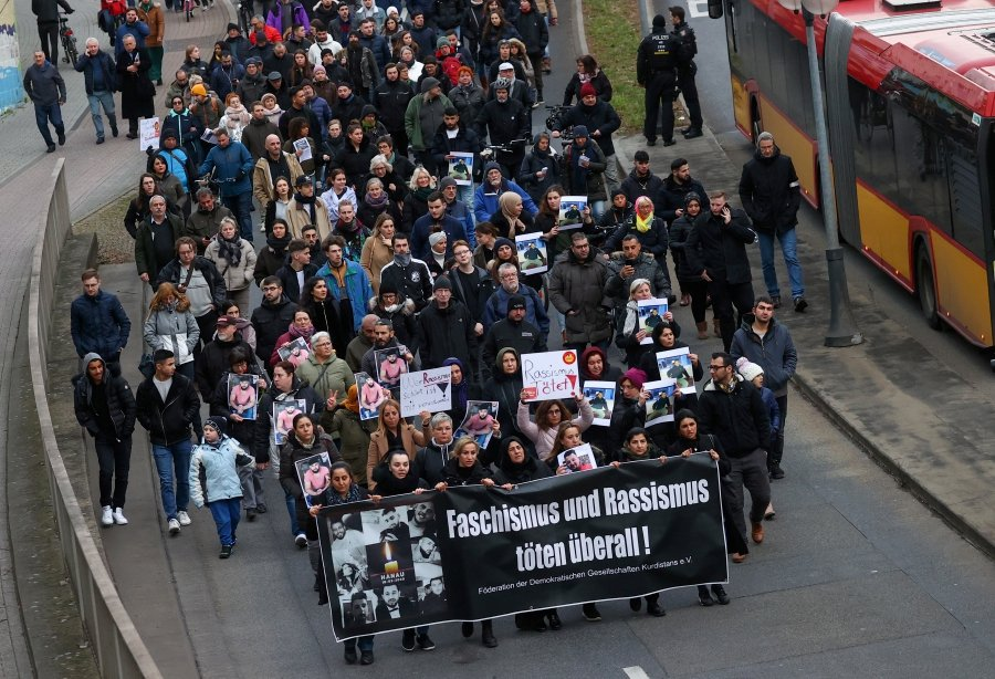 People hold banners as take part in a vigil for the victims of a shooting, in Hanau, near Frankfurt, Germany, February 21, 2020. - REUTERS/Kai Pfaffenbach