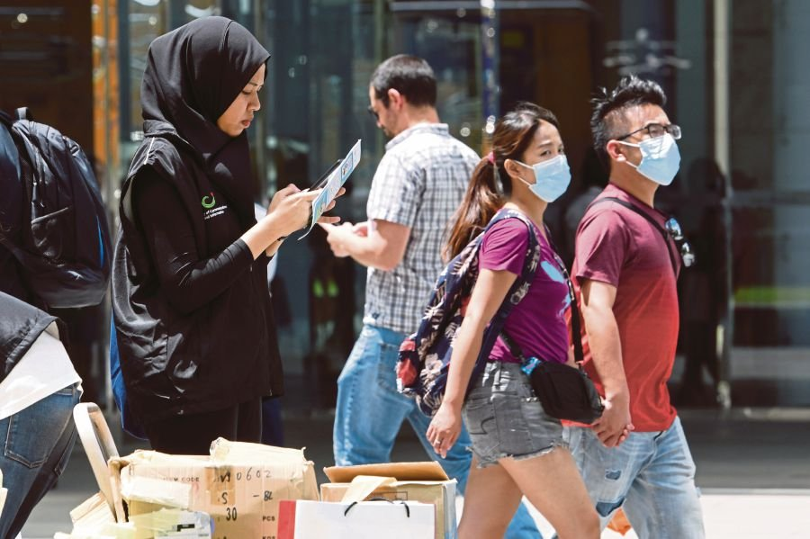 A volunteer from Singapore's Ministry of Communication prepares to collect feedback from members of the public on the current novel coronavirus outbreak situation during lunch break at the Raffles Place financial business district in Singapore on February 5, 2020. (Photo by Roslan RAHMAN / AFP)