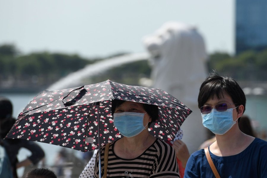Visitors wear protective face masks at the Marina Bay waterfront in Singapore. - (Photo by Roslan RAHMAN / AFP)