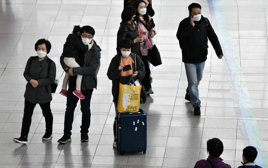 People wearing face masks walk through at a railway station in Seoul on March 21, 2020. - South Korea is planning to send two chartered flights to Italy to evacuate some 570 citizens from the country with the most deaths from the coronavirus pandemic, reports said. (Photo by Jung Yeon-je / AFP)