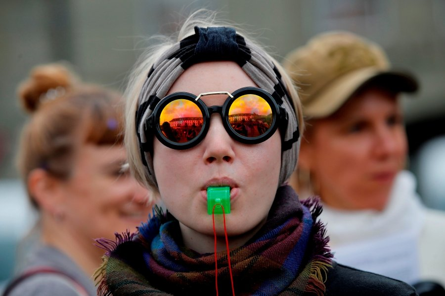 Women whistles during a nation-wide women's strike for wage parity, on June 14, 2019 in Swiss capital Bern. - Nearly 30 years after staging a first strike, women across Switzerland stage mass demonstrations for for equal pay. - AFP