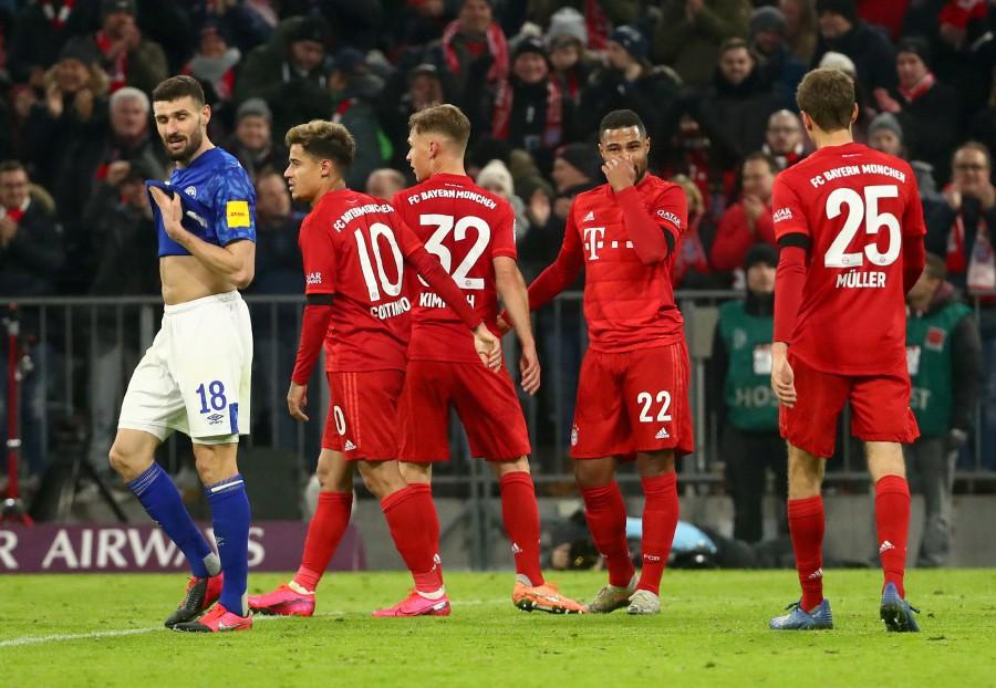 Bayern Munich's Serge Gnabry celebrates scoring their fifth goal as Schalke's Daniel Caligiuri looks dejected. -Reuters
