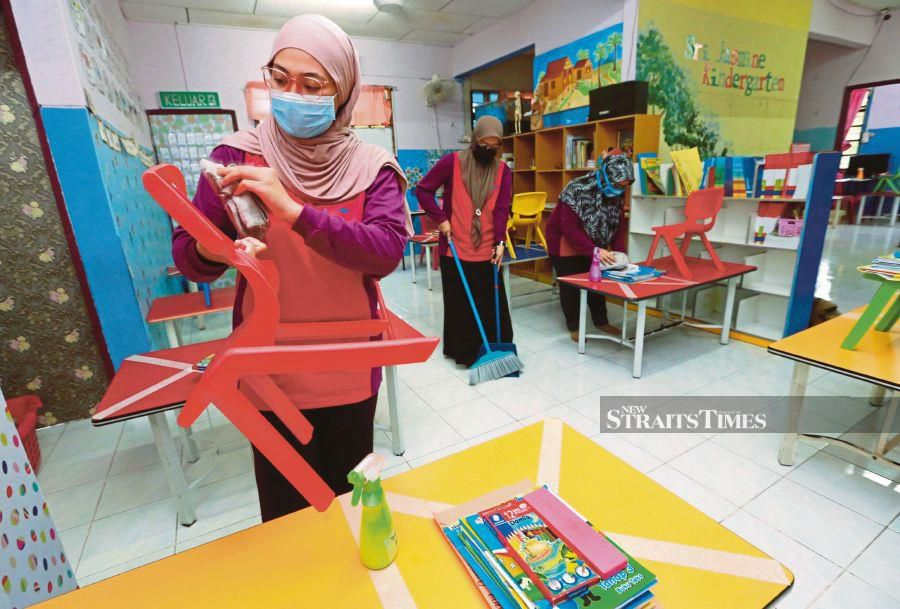 This June 15 pic shows staff at Tadika Integrasi Sri Jasmine, Taman Setiawangsa making preparations  for the reopening of the kindergarten. - NSTP/FATHIL ASRI.