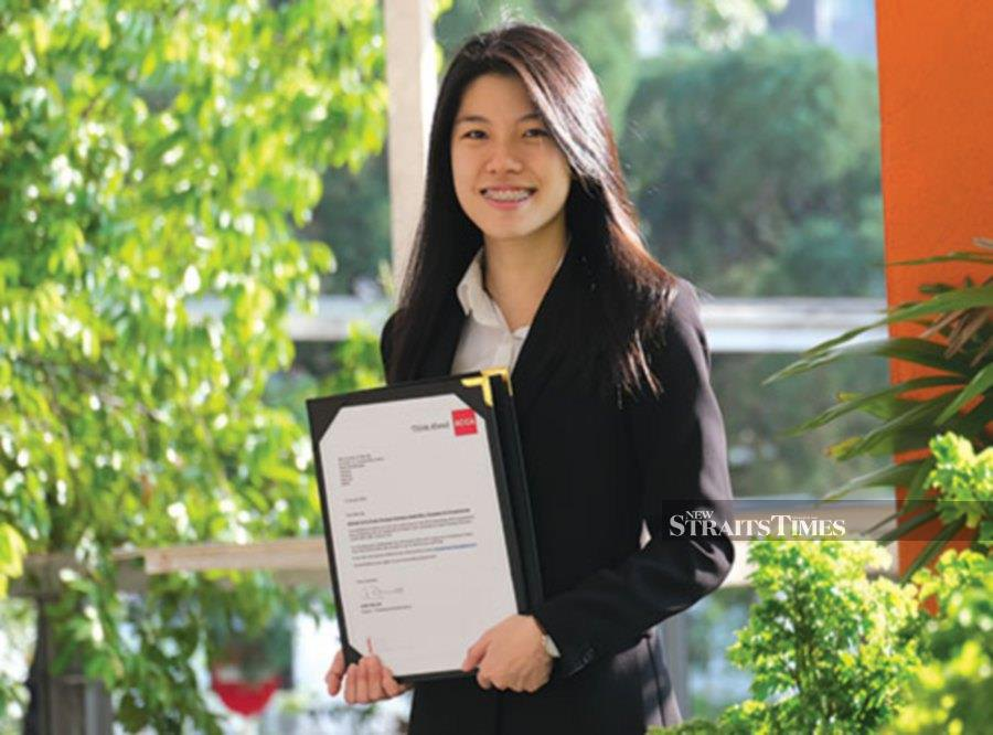 Caroline Ng Yi-Wye holding the letter of her achievement in the recent ACCA exam.