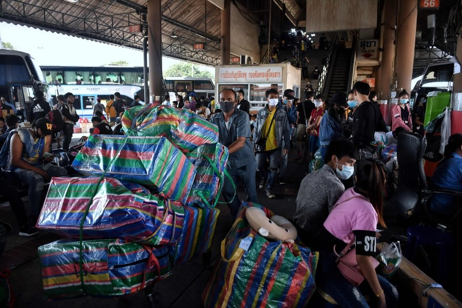 Passengers wait to board buses with their belongings as thousands of migrant workers try to leave the Thai capital for their home provinces amid concerns over the spread of the COVID-19 coronavirus, at Mo Chit Bus Terminal in Bangkok on March 23, 2020. (Photo by Lillian SUWANRUMPHA / Lillian SUWANRUMPHA / AFP)