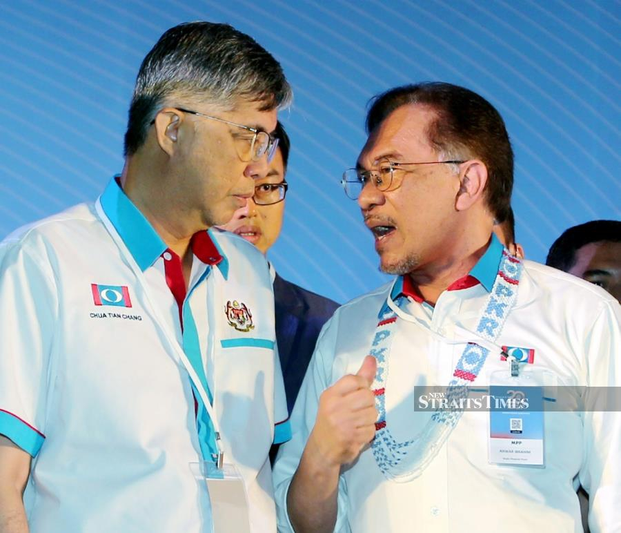 PKR president Datuk Seri Anwar Ibrahim (right) talking to vice-president Tian Chua at the party's national congress in Melaka yesterday. PIC BY RASUL AZLI SAMAD