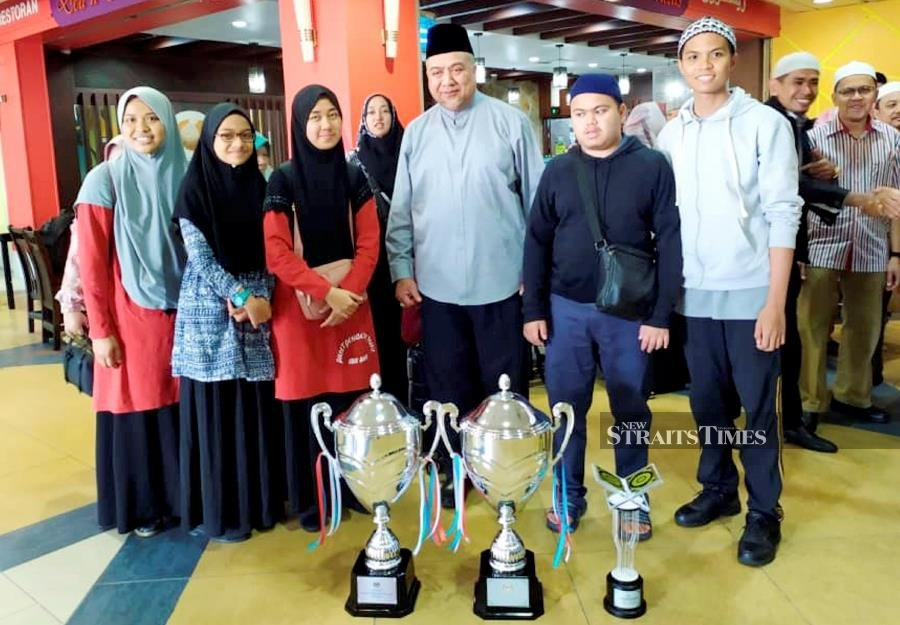 Fresh from their victory at the 1441H/2020M National Quran recital competition last night, Muhammad Qayyim Nizar Sarimi and Putri Aminah Mohd Hanif were greeted by some 50 family members and friends at Sultan Ismail Petra Airport, Pengkalan Chepa, at about 1pm today. - NSTP/Courtesy of JAHEAIK