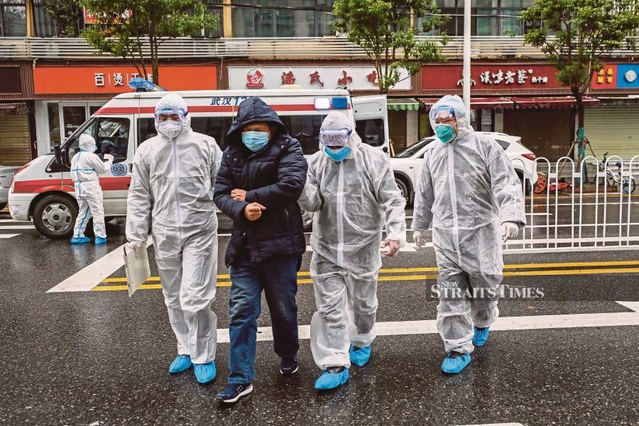 TOPSHOT - This photo taken on January 26, 2020 shows medical staff members wearing protective clothing to help stop the spread of a deadly virus which began in the city, accompanying a patient (2nd L) as they walk into a hospital in Wuhan in China's central Hubei province. - China on January 27 extended its biggest national holiday to buy time in the fight against a viral epidemic, as the death toll spiked to 81 despite unprecedented quarantine measures and travel lockdowns. AFP