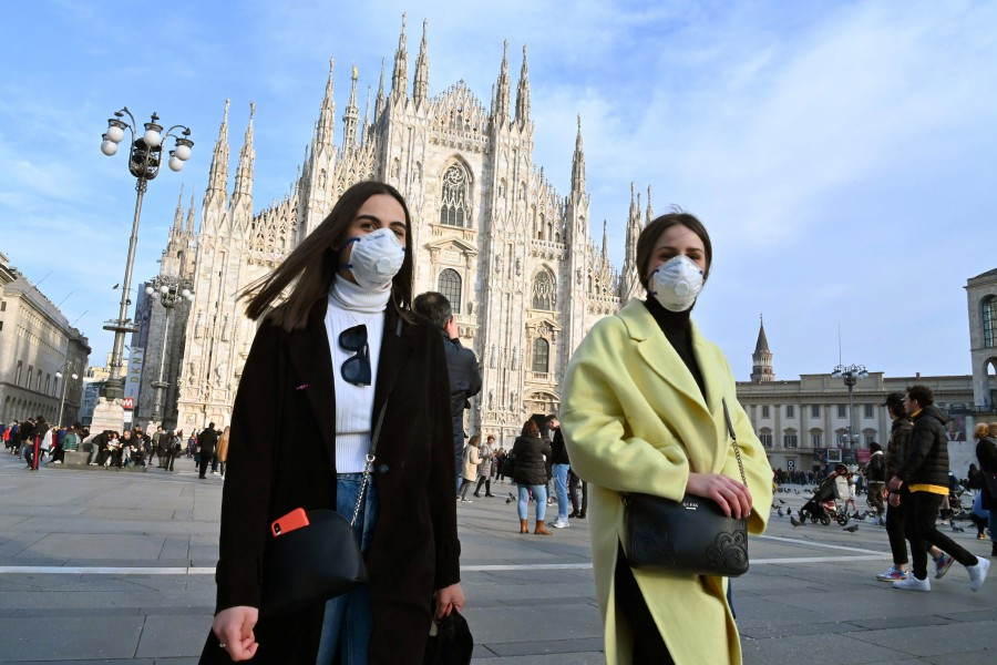 TOPSHOT - Woen wearing a respiratory mask walk across Piazza del Duomo in central Milan. -AFP