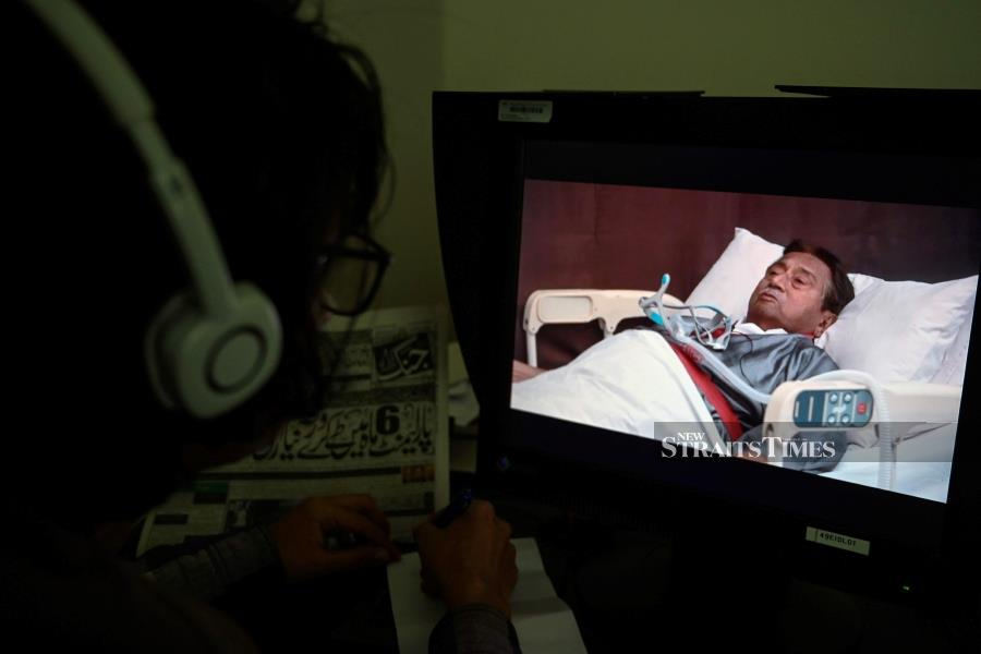 """A journalist watches a video statement of the ailing exiled former Pakistani military ruler Pervez Musharraf in a hospital bed in Dubai, in Islamabad on December 19, 2019. - Exiled former Pakistan military leader Pervez Musharraf dismissed the unprecedented treason conviction and death sentenced handed to him earlier this week, saying the ruling was the result of a """"personal vendetta"""". AFP"""