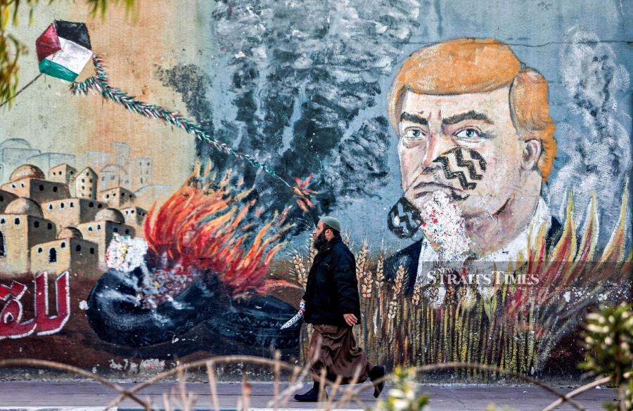 A Palestinian walks past a graffiti mural depicting US President Donald Trump with a footprint on his face, along a street in Gaza City on January 28, 2020. AFP