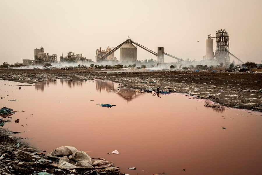 Smoke rises in-front of the SOCOCIM cement factory as artisanal fish smokers work along the coastline in Bargny on June 16, 2020. - The coastline of Bargny is well known for being an environmental disaster. The small fishing village caught between a cement factory, an old coal factory and hundreds of Senegalese smoking fish along the shoreline that is exported throughout West Africa. (Photo by JOHN WESSELS / AFP)