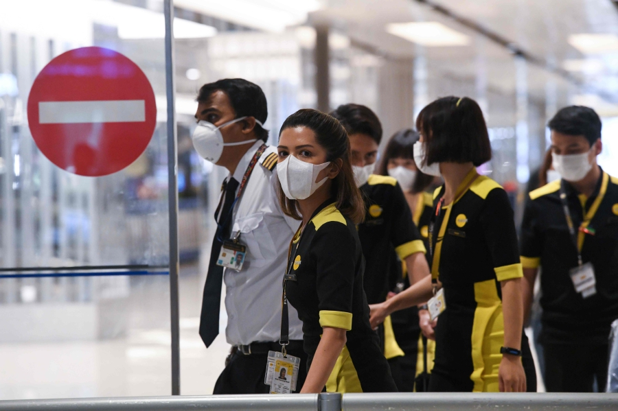 The flight crew of the chartered Scoot airline which flew to Wuhan to evacuate Singaporean nationals arrive at Changi international airport on Singapore on January 30, 2020. - A group of Singaporean nationals evacuated from Wuhan, the Chinese city at the centre of a deadly virus outbreak, arrived in Singapore on January 30 aboard a charter plane. AFP