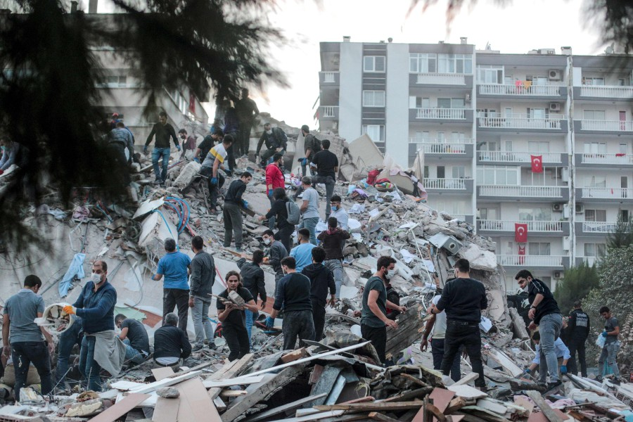Volunteers clear rubbles as they search for survivors in a collapsed building after a strong earthquake struck the country's western coast and parts of Greecen killing four people and injuring 120, in Izmir, on October 30, 2020. - A powerful earthquake hit Greece and Turkey, causing buildings to collapse and a sea surge that flooded streets in the Turkish resort city of Izmir. Greek public television said the quake also caused a mini-tsunami on the eastern Aegean Sea island of Samos, damaging buildings. The US Geological Survey said the 7.0 magnitude quake was registered 14 kilometres (8.6 miles) off the Greek town of Karlovasi on Samos. (Photo by Mert CAKIR / AFP)