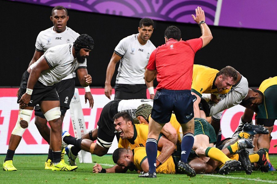 Australia's hooker Silatolu Latu (bottom) scores a try during the Japan 2019 Rugby World Cup Pool D match against Fiji at the Sapporo Dome in Sapporo. - AFP