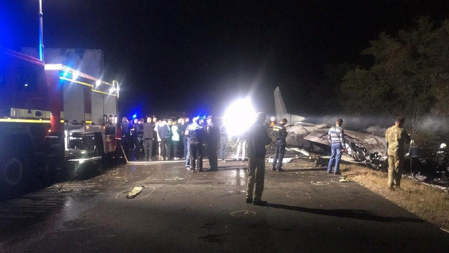 "This handout picture taken and released by the State Emergency Service of Ukraine on September 25, 2020 shows rescuers working on the place of the Antonov-26 transport aircraft crash at Chuhuiv military air base, 30 kilometres southeast of Kharkiv. - Ukraine's interior ministry on September 25, 2020 said at least 20 people were killed when a military plane crash landed in the Kharkiv region in the east of the country. Ukraine's air force said the Antonov-26 transport plane was carrying crew and cadets. The interior ministry said there were ""20 dead and two seriously injured"" among the 24 passengers. (Photo by - / State Emergency Service of Ukraine / AFP)"