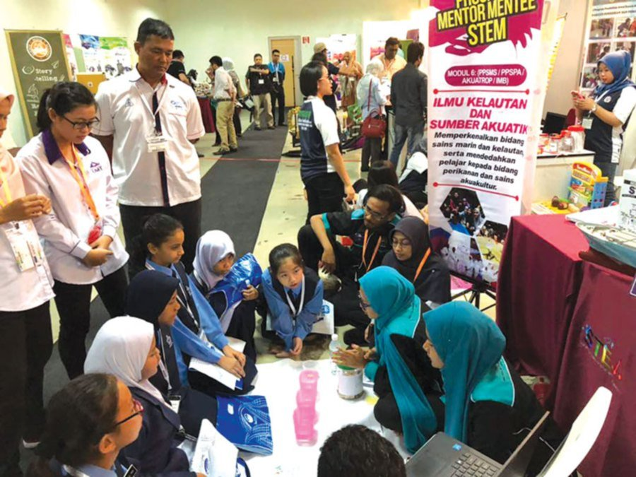 Schoolchildren listening to mentors at the UTM booth. The cover picture shows a UPSI physics department lecturer (right) demonstrating an experiment using the Pascal lab kit.
