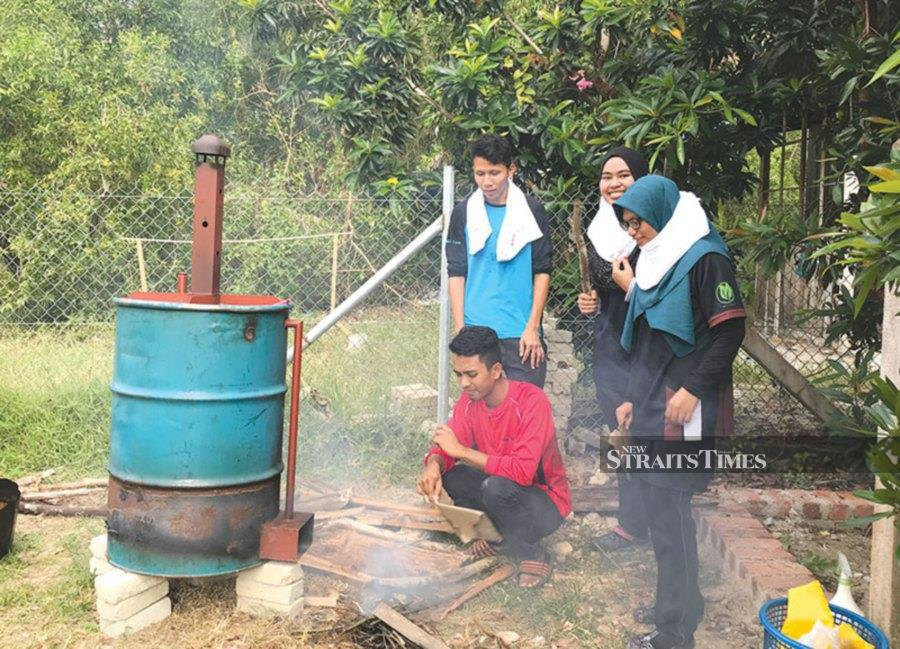 UMT students burning waste materials to create biochar for the strawberry farm.