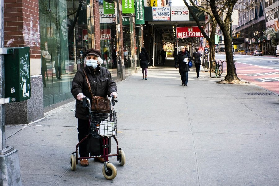 An elderly woman wears a face mask and plastic gloves as she waits to cross the street due on March 26, 2020 in New York City. Across the country schools, businesses and places of work have either been shut down or are restricting hours of operation as health officials try to slow the spread of COVID-19. Eduardo Munoz Alvarez/Getty Images/AFP