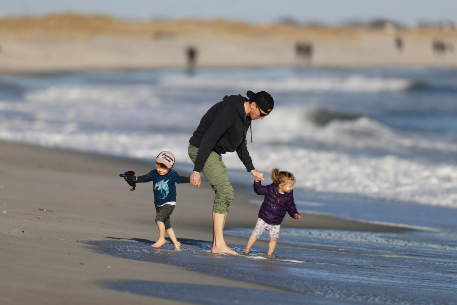"""LIDO BEACH, NEW YORK - MARCH 21: A Father plays with his children at Lido Beach on March 21, 2020 in Lido Beach, New York. Yesterday New York Governor Andrew Cuomo announced he was putting the state on """"pause"""" meaning non essential workers should stay home at all times except for critical travel due to the coronavirus pandemic. The World Health Organization declared coronavirus (COVID-19) a global pandemic on March 11th. Al Bello/Getty Images/AFP"""