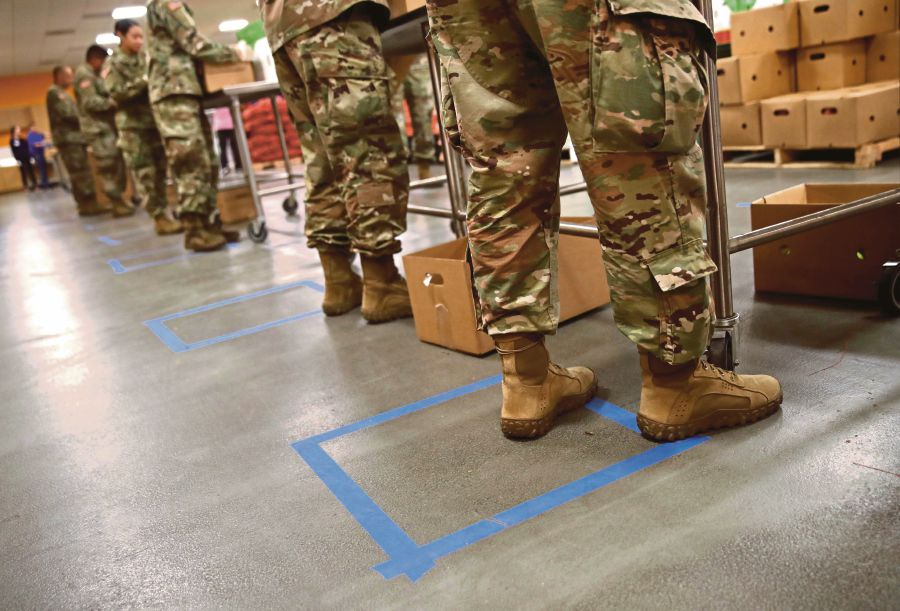 Members of the California National Guard 115th Regional Support Group standing practice social distancing as they help pack boxes of food at the Second Harvest Food Bank of Silicon Valley in San Jose, California. -AFP pic