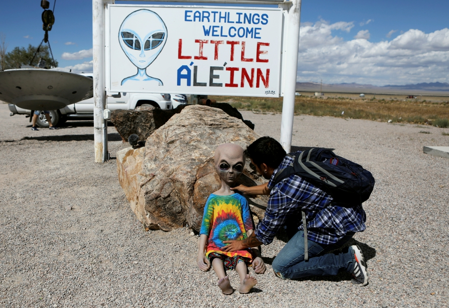 An attendee poses an alien doll at the Little A'Le'Inn as an influx of tourists responding to a call to 'storm' Area 51, a secretive U.S. military base believed by UFO enthusiasts to hold government secrets about extra-terrestrials, is expected in Rachel, Nevada, U.S.-Reuters
