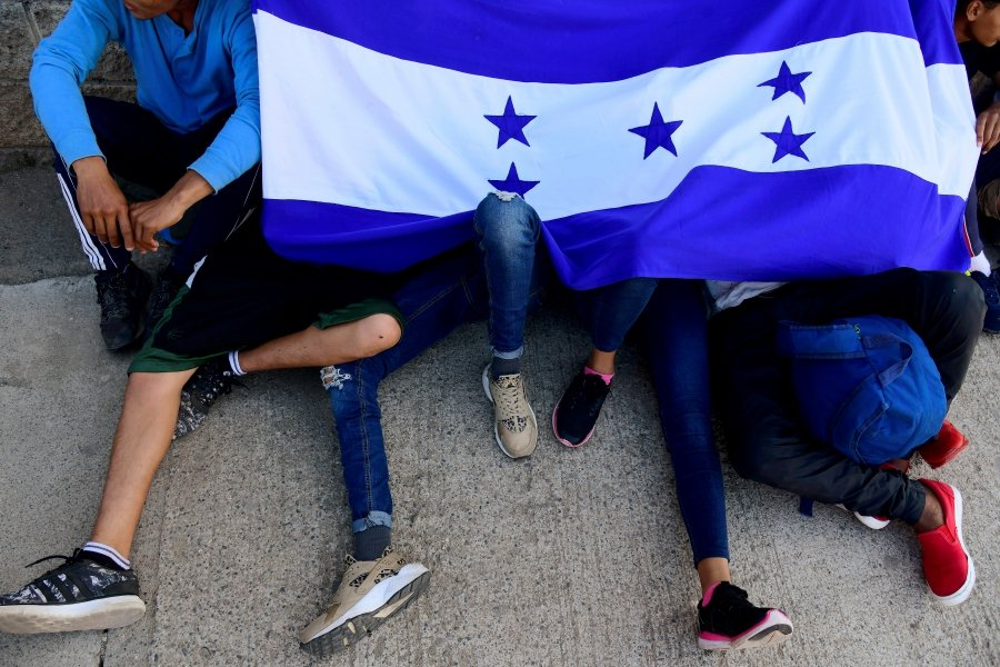 Hondurans hold a Honduran national flag as they wait to leave with a new caravan of migrants, set to head to the United States, at a bus station in San Pedro Sula, Honduras January 14, 2020.-Reuters
