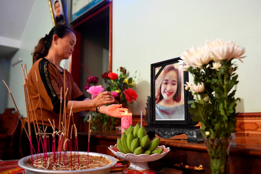 A relative lights an incense stick infront of a portrait of Bui Thi Nhung, who is feared to be among the 39 people found dead in a truck in Britain, inside her house in Vietnam's Nghe An province on October 26, 2019. - A photo of her missing daughter Bui Thi Nhung, an offering of fruit and a bouquet of flowers -- a makeshift shrine laid by a desperate mother in a remote Vietnamese town many fear was home to some of the 39 people found dead in a truck in Britain. More than 20 Vietnamese are feared to be among the bodies found in a refrigerated trailer in an industrial park in Essex east of London on October 23. (Photo by NHAC NGUYEN / AFP)